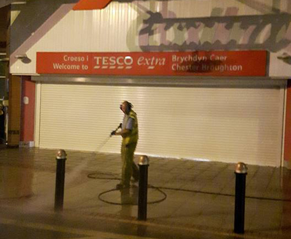 Man outside a Tesco Extra using a pressure washer on the pavement.